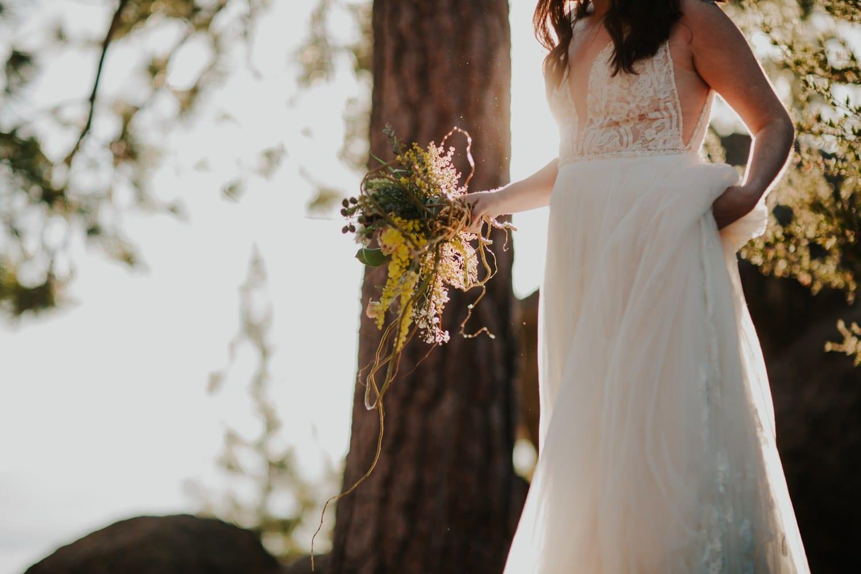 Bride holding wedding dress at Lake Tahoe