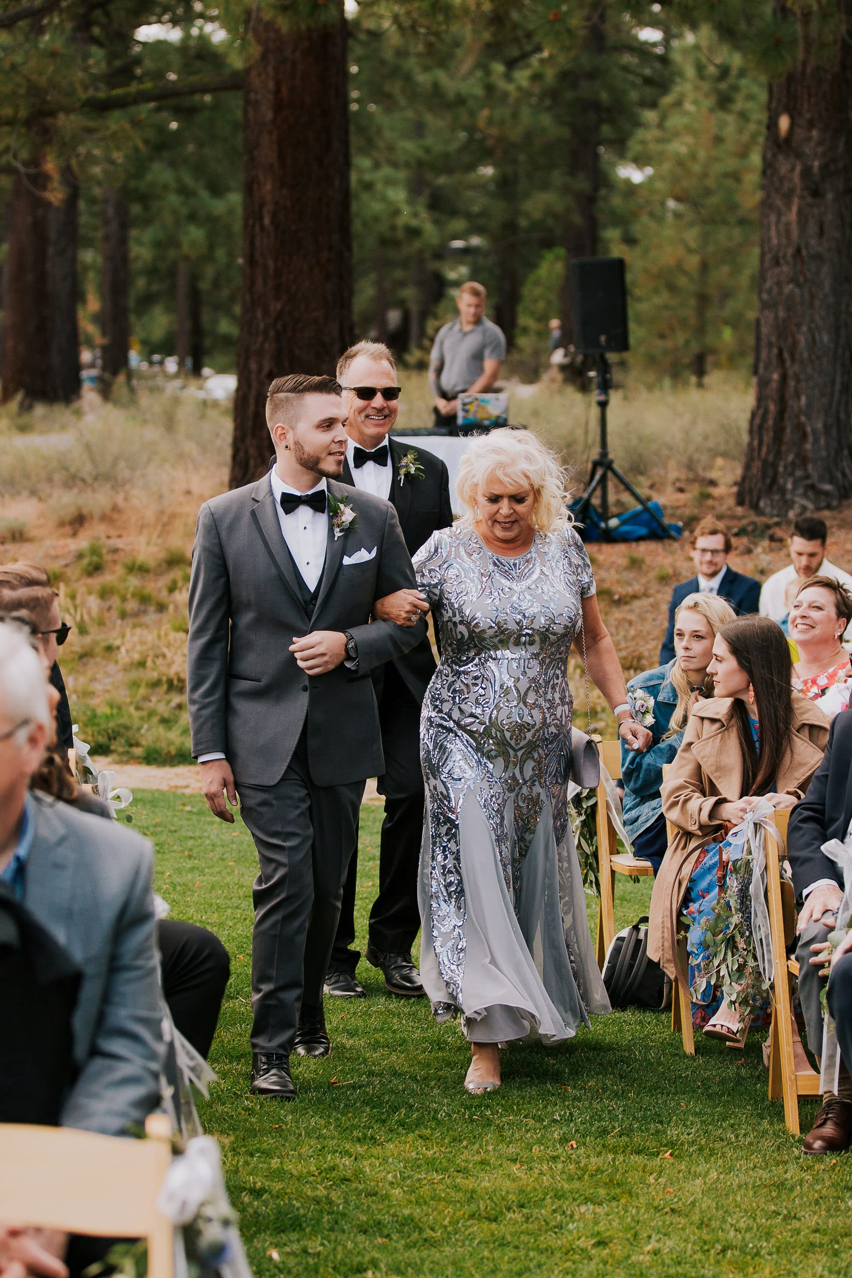 groom and mom walk down the aisle in summer outdoor ceremony