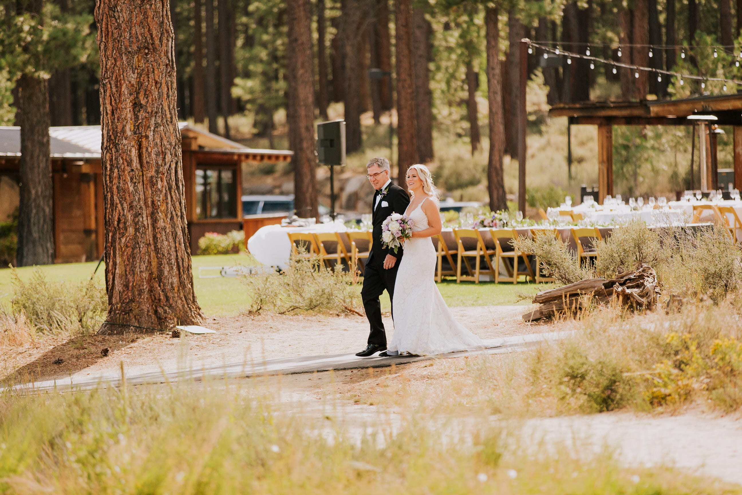 bride's father escorts bride down aisle in outdoor Truckee California wedding ceremony