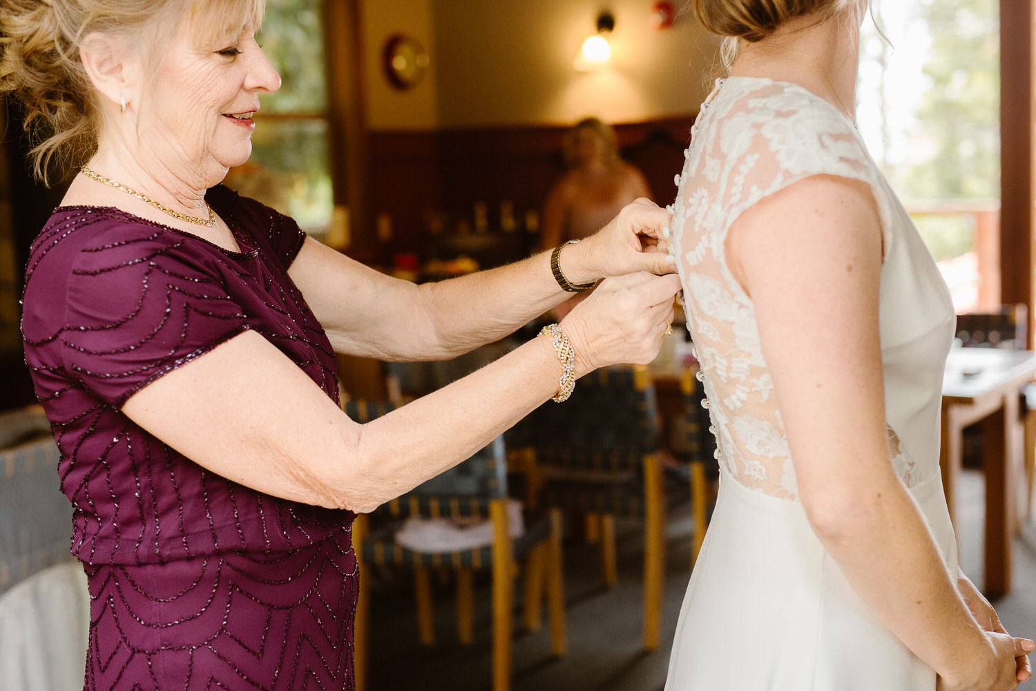 bride gets dressed in Evergreen Lodge in Yosemite for wedding