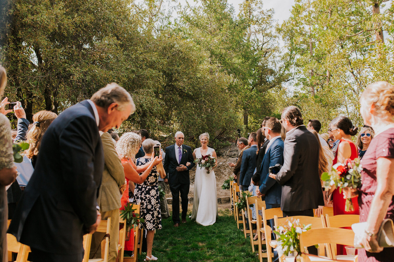 bride and father walk down aisle at the Evergreen Lodge